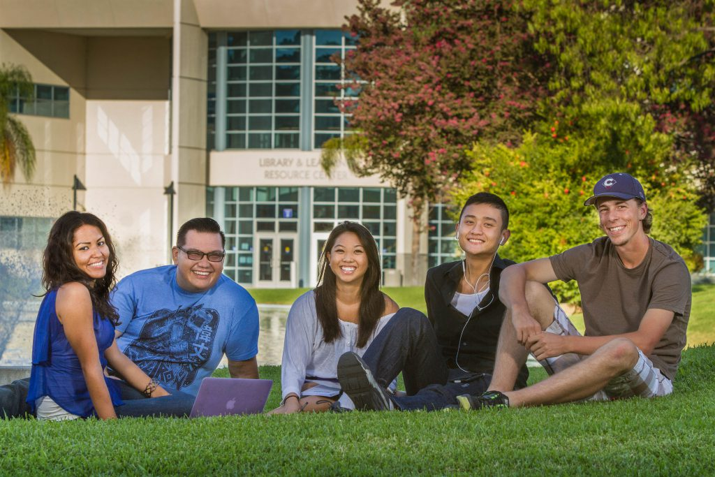 Cypress College students seatedthe campus pond.