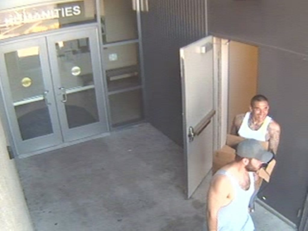 Two burglary suspects are seen exiting the Humanites Building on Saturday, August 16, 2014. The suspect in the white tank-top was reported by Officers of the Cypress Police Department to have been carrying a gun. He is unidentified and remains at large. The suspect wearing the grey baseball-style cap was arrested shortly after this image was captured. He is known to Campus Safety Officers and considered to be dangerous. Anyone who sees either suspect should avoid contact and contact police or Campus Safety when it's safe to do so.