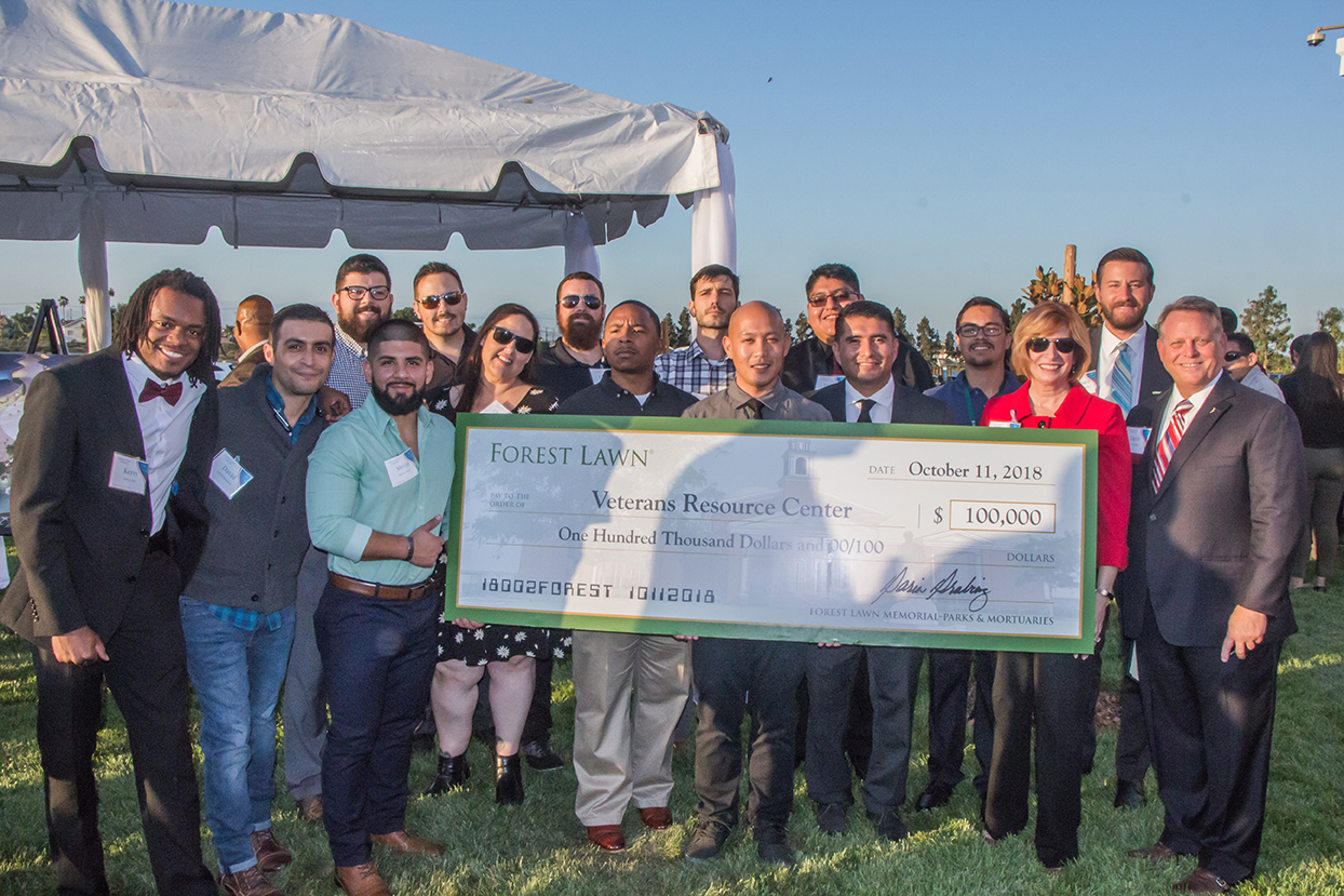 Cypress College President Dr. Schilling and student veterans accept a $100,000 check from Forest Lawn to support the VRC